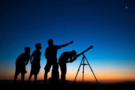 O pai e três filhos olhando através de um telescópio