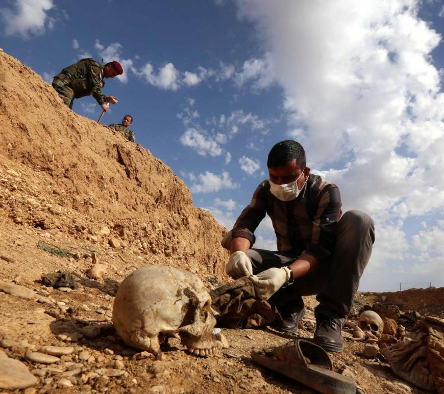 No Iraque homem inspeciona os restos mortais de Yazidis mortos pelo Isis e enterrados em uma vala coletiva perto da vila de Sinuni.
